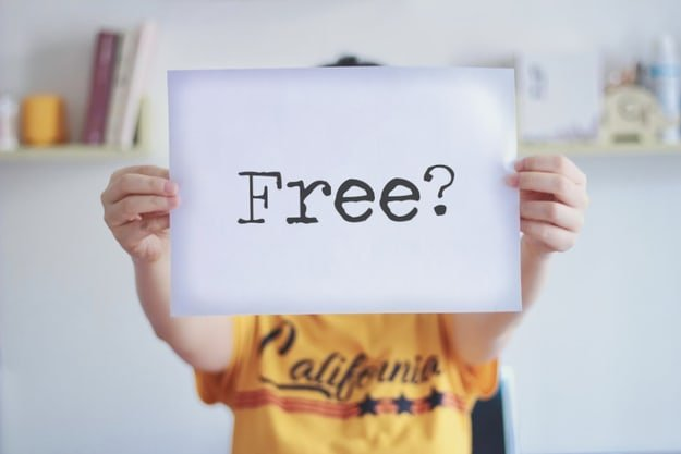 "woman holding a white piece of paper with the question ""free?"" written on it"