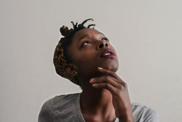 black woman staring at the top with her left hand touching her chin while thinking about something
