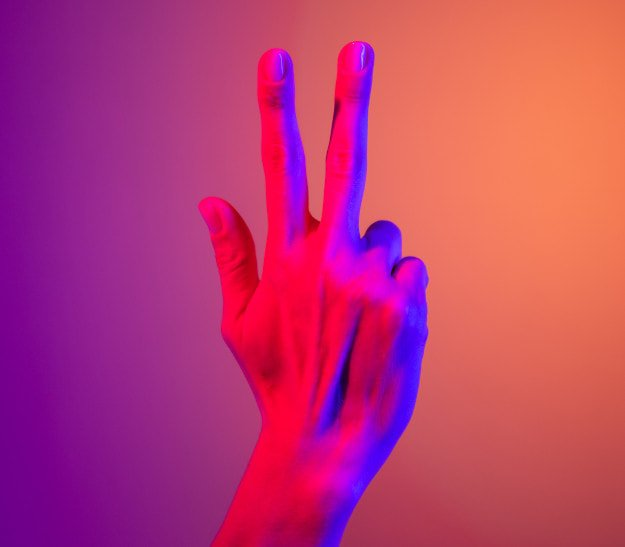 person's hand showing three fingers