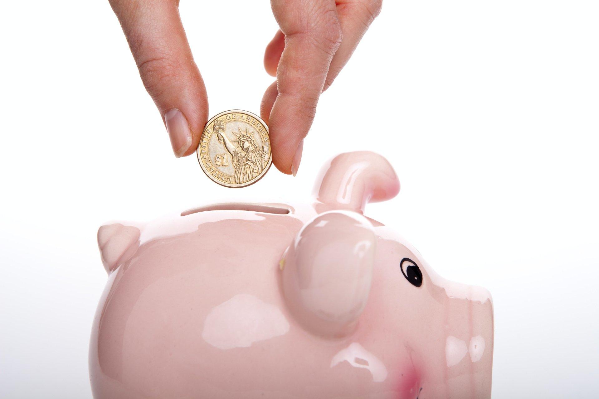 a hand putting a coin inside a piggy bank