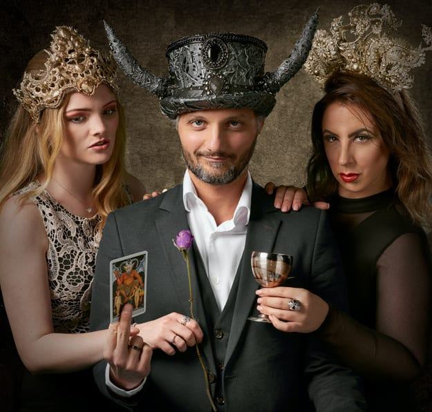 one man wearing a hat with 2 horns, with two women on both sides of him
