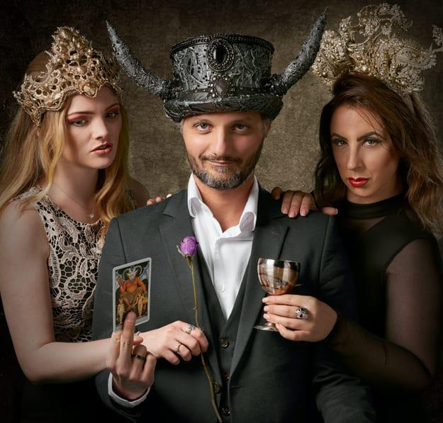 un hombre vistiendo un sombrero con 2 cuernos, acompañado con 2 mujeres a ambos lados de él