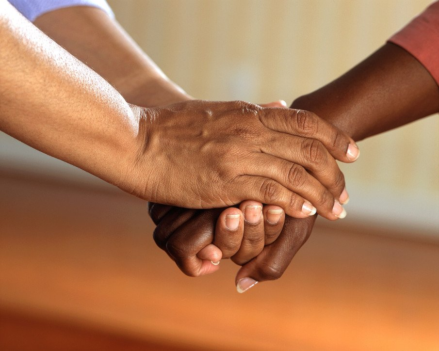 two hands of a person holding another someone else's hand in support