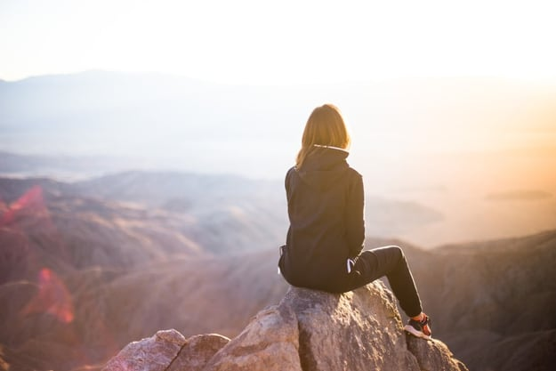 woman sitting on top of a mountain staring at the horizon and the sun