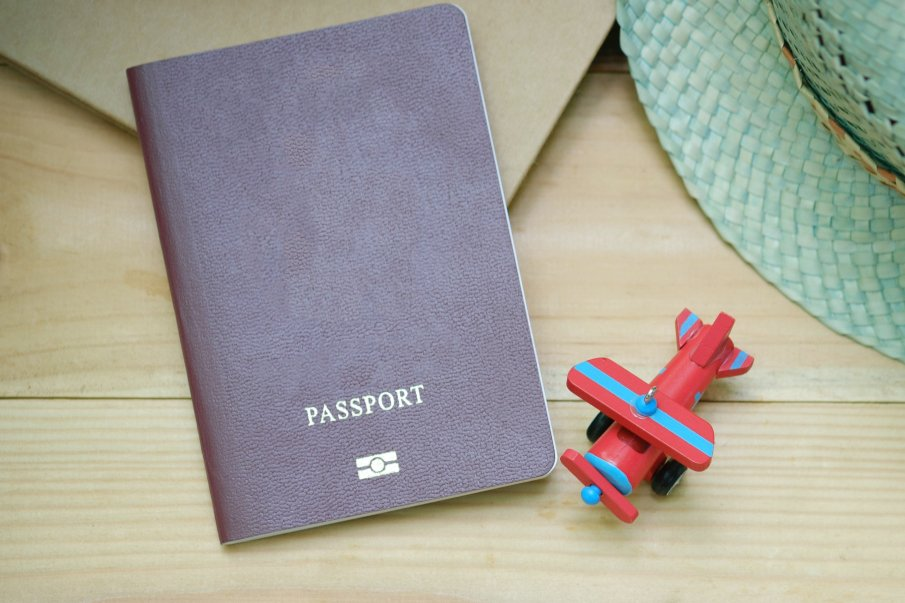 a passport with a small plane toy next to it