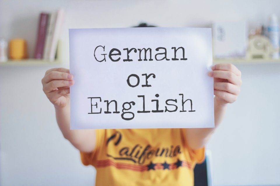 "a woman holding a white paper with the words ""german or english"""