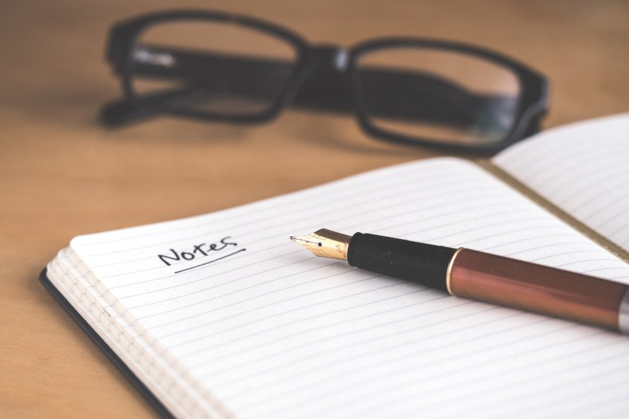 photo of a pen, a notebook and a pair of glasses