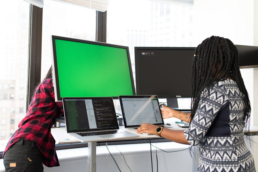 a woman doing some cable work on a monitor and another woman looking at the screen