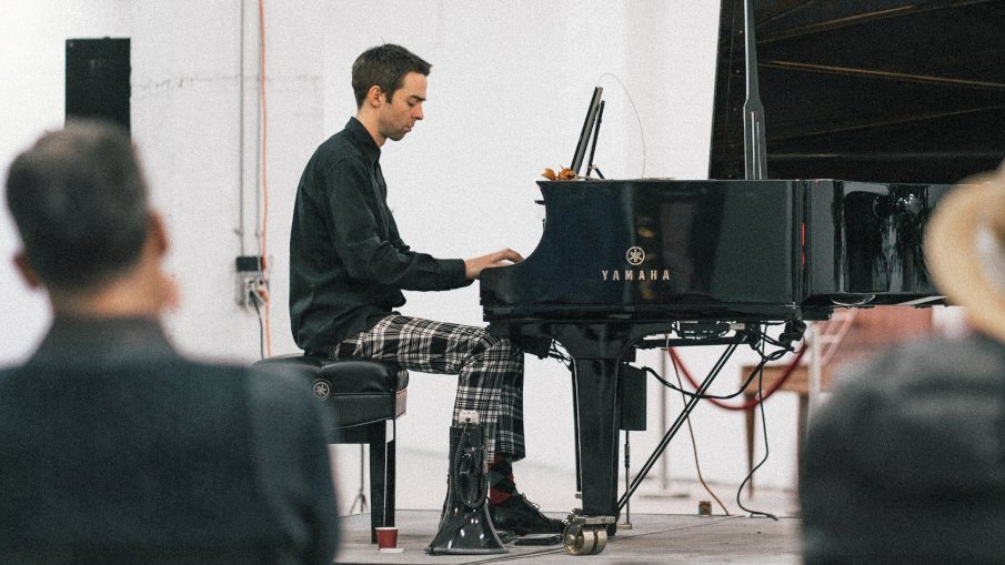 guy playing piano being evaluated by his teacher