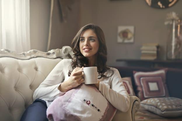 una chica con una taza en su mano derecha mirando feliz hacia el horizonte, sintiéndose calmada y relajada