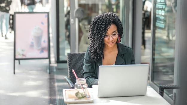 black woman using her laptop to browse master programs in My German University