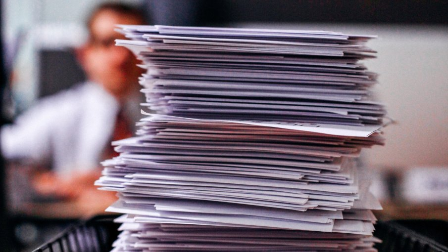 pile of documents with a guy in the background and out of focus