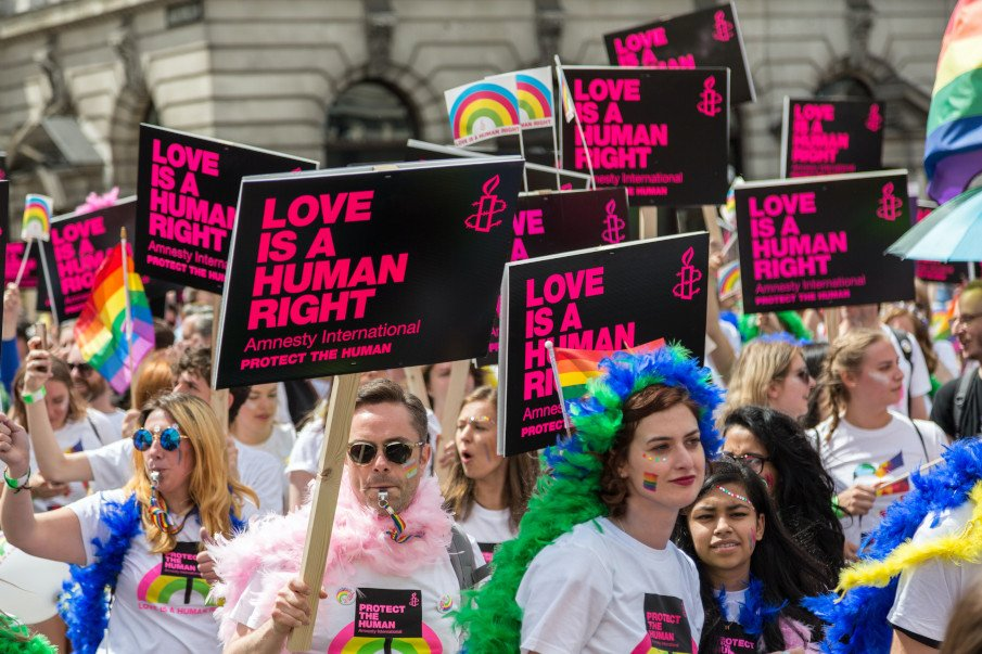 """people with signs with the slogan """"love is a human right"""""""