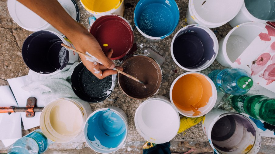 a painter with a lot of buckets containing paint of different colors