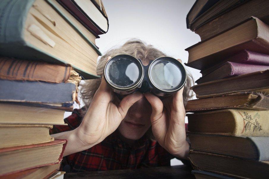 guy looking through his binoculars with books around him