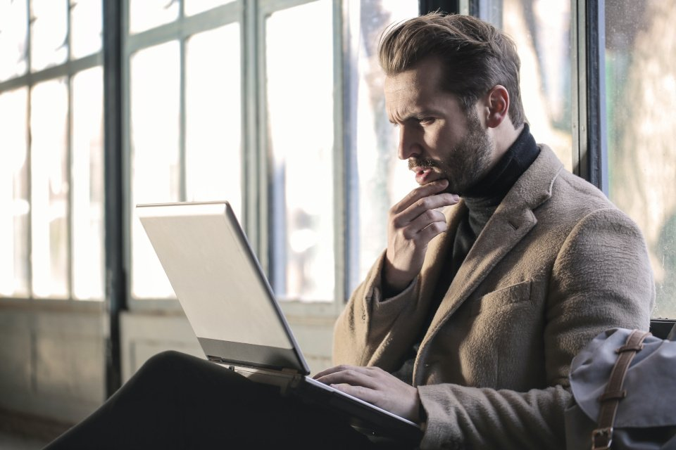 man sitting on the floor with his laptop on his legs staring at his laptop thinking about something