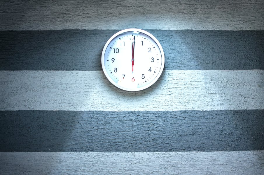 a clock on a wall with blue stripes