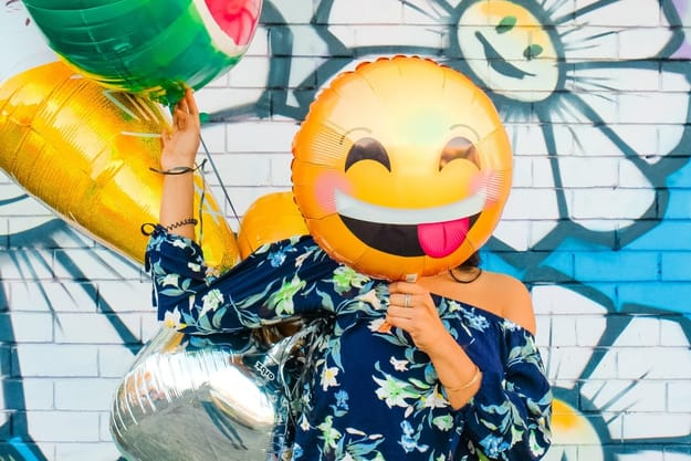 a woman putting an emoji balloon of a happy face in front of her face