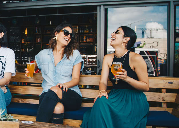 two woman having some drinks very happy