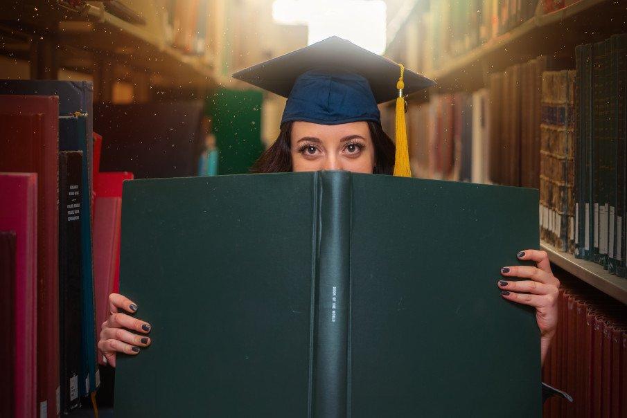 girl wearing her graduation cap behind a big green book