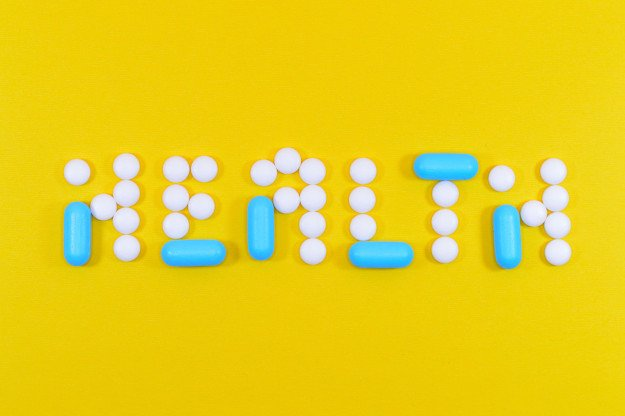 white and blue pills forming the word Health