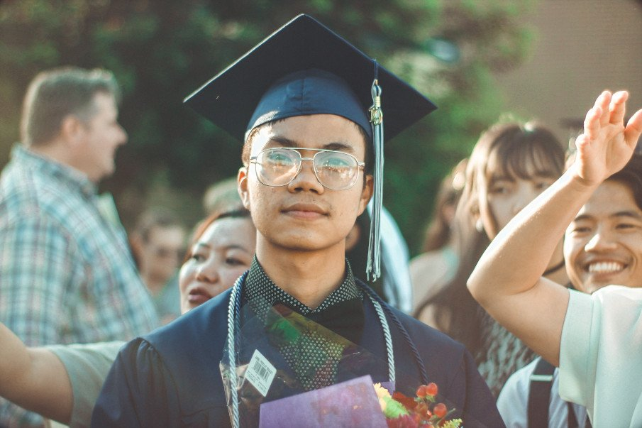asian guy on the day of his graduation wearing a gown and graduation cap