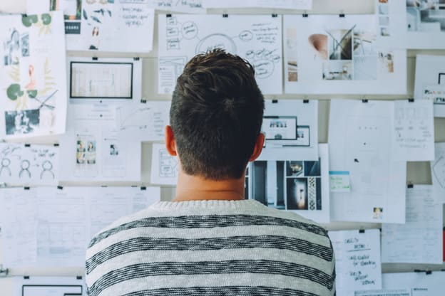 un chico mirando una pared llena de papeles con sus planes