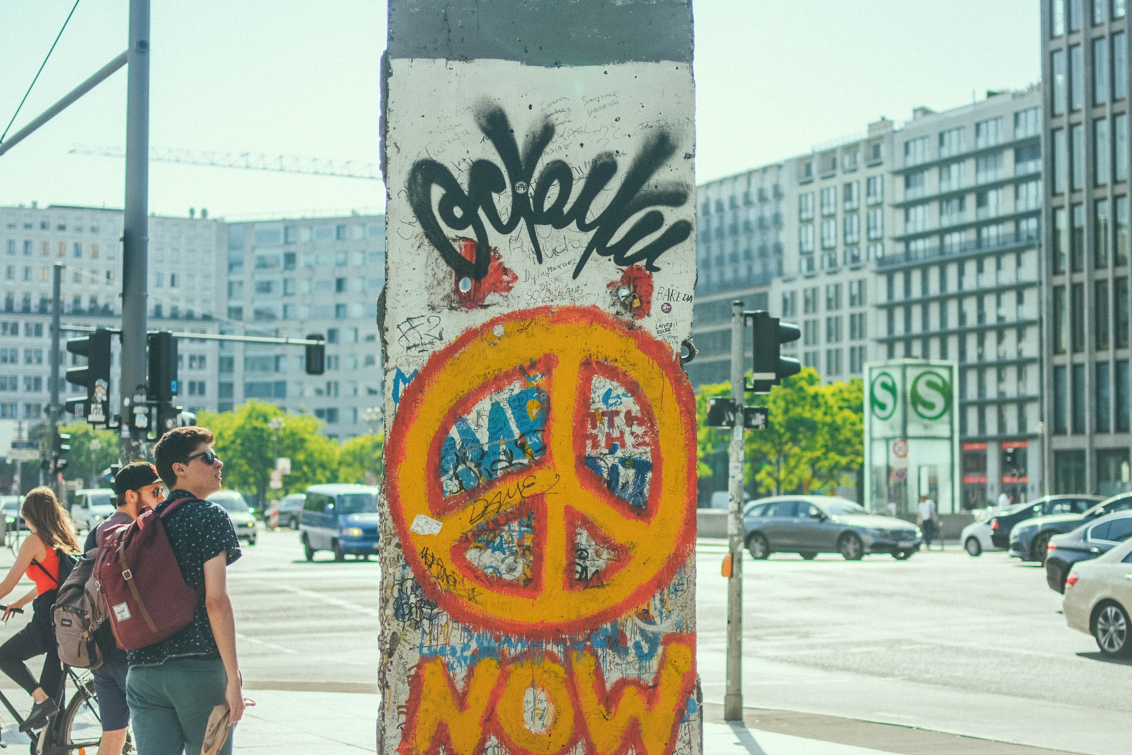 young tourists next to a part of the Berlin wall