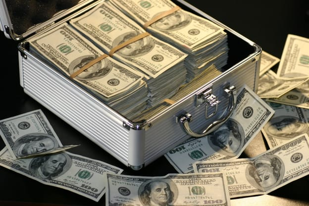 grey metal suitcase with a pile of dollar bills