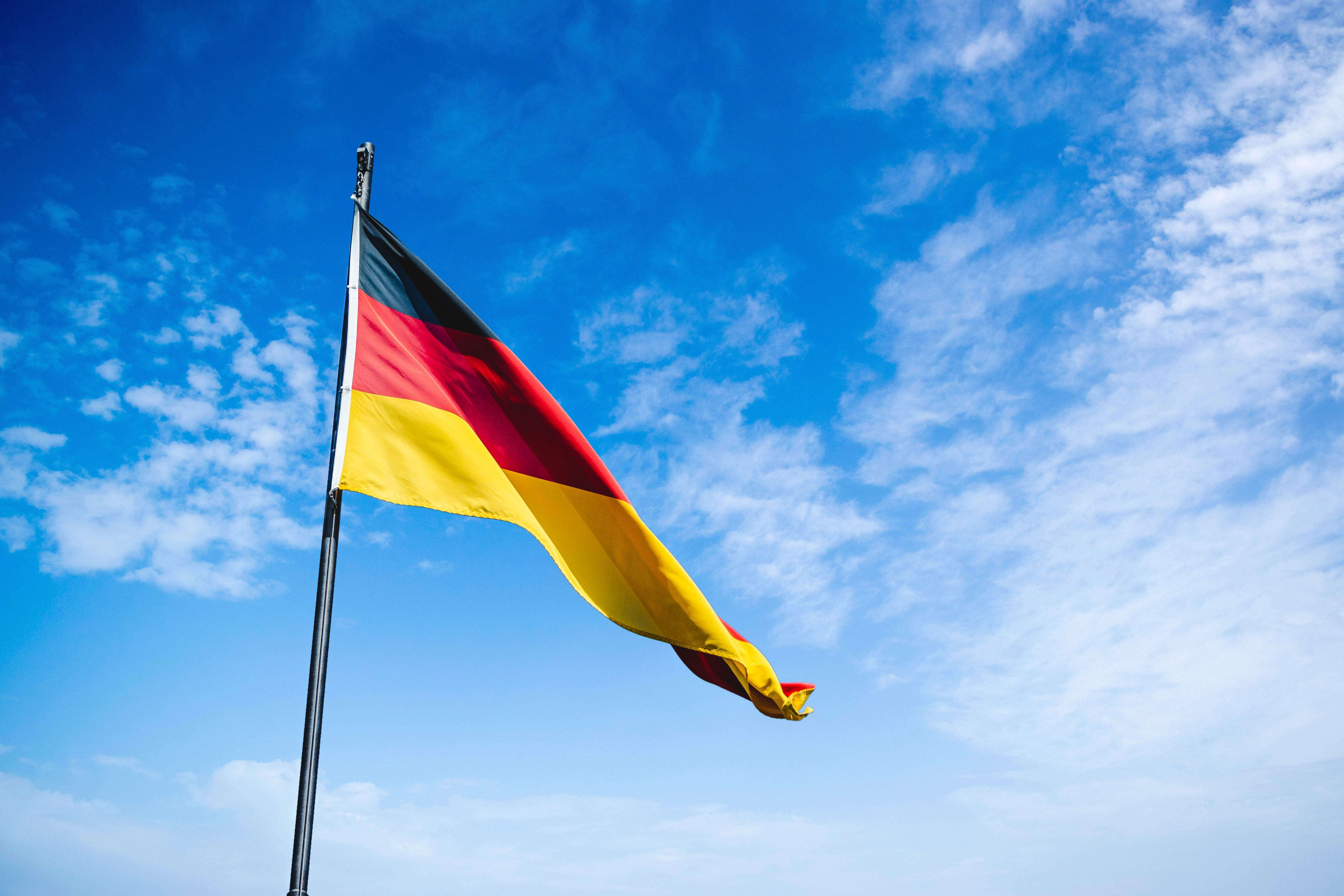 photo of the german flag with a blue sky and some clouds in the background